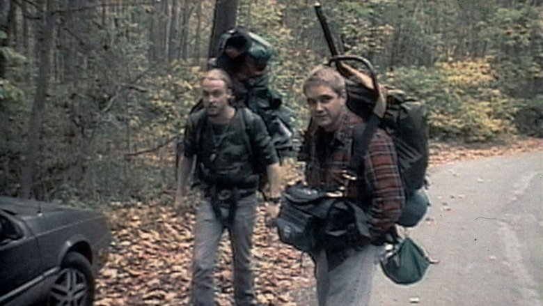 Josh and Mike with backpacks on hiking into the woods