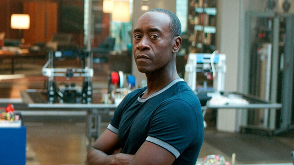Don Cheadle stands in a lab with arms crossed