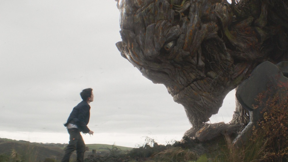A boy faces a giant tree monster